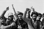 Group of men carrying arms and ammunitions raise their hands while picture id957403680?s=170x170