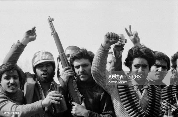 A group of men carrying arms and ammunitions raise their hands victoriously while driving around the city after having looted army garrisons in the...
