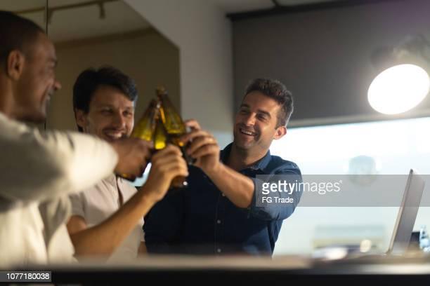 残業後のオフィスでは、ビールを飲む男性同僚のグループ - 仕事後 ストックフォトと画像