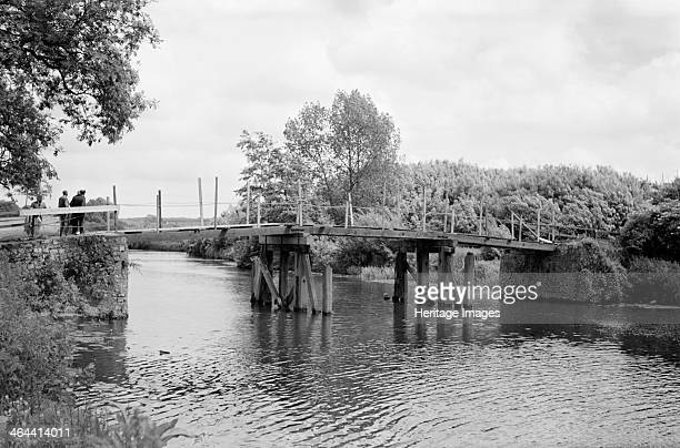 A group of men contemplate a footbridge over the River Medway at Barming Kent c1945c1965 A temporary walkway has been laid over the old bridge...