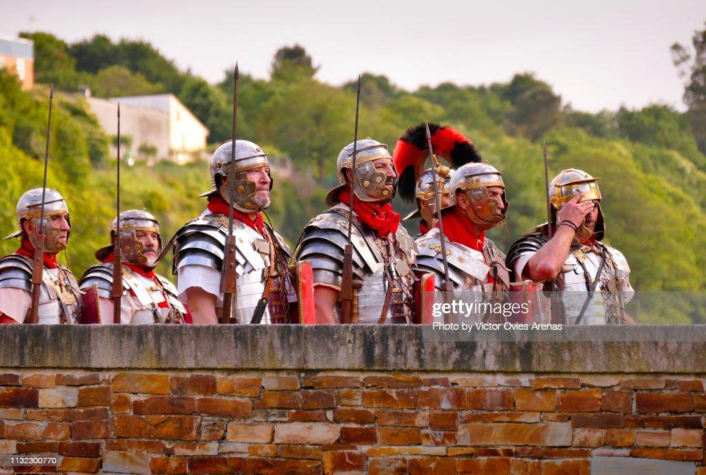 Group of men disguised as Roman legionaries crossing the ancient Roman bridge during the Arde Lvcvs festival in Lugo, Galicia, Spain : Foto de stock