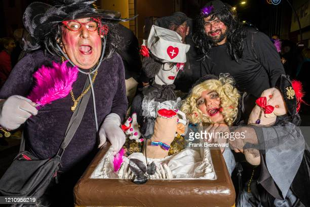 Group of men, dressed up as women in mourning clothes and carrying a dildo, partying in the streets during the funeral procession Burial of the...