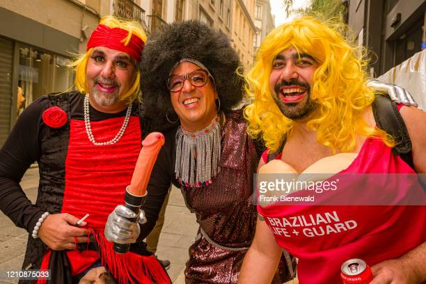 A group of men dressed up as women wearing pink wigs carrying a dildo and smiling partying in the streets during the Daytime Carnival