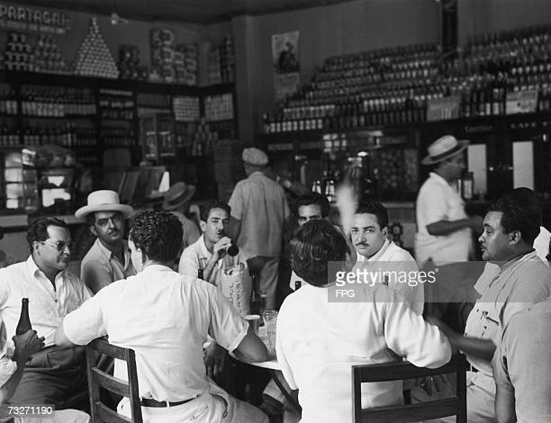A group of men drinking beer in a bar in Santiago Cuba 1950s