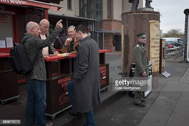 A group of men eating snacks beside a man dressed as an East German soldier at the East Side Gallery a section of the former Berlin Wall on the...