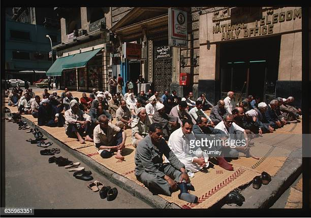 A group of men face Mecca on a Cairo sidewalk and prepare to pray
