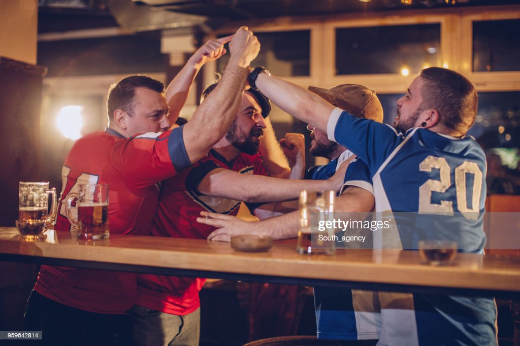 Group of men fighting in sports pub : Stock Photo