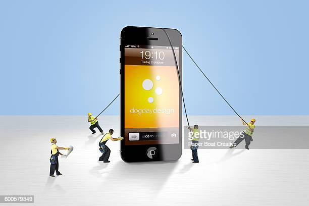 group of men fixing a giant smart phone