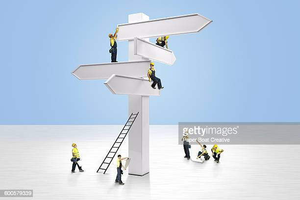 group of men fixing giant road signs - small stock pictures, royalty-free photos & images