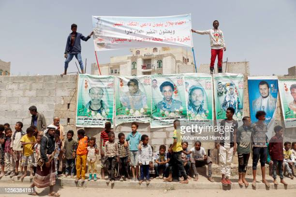 Group of men from the Al-Muhamasheen community hold banners showing the Houthi movement's 1-leader Abdulmalik Badr Aldin Al-Houthi and their...