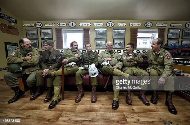A group of men from the Wartime Living History Association dressed as American GI's sit in the waiting room of the Headhunters Barber Shop and...