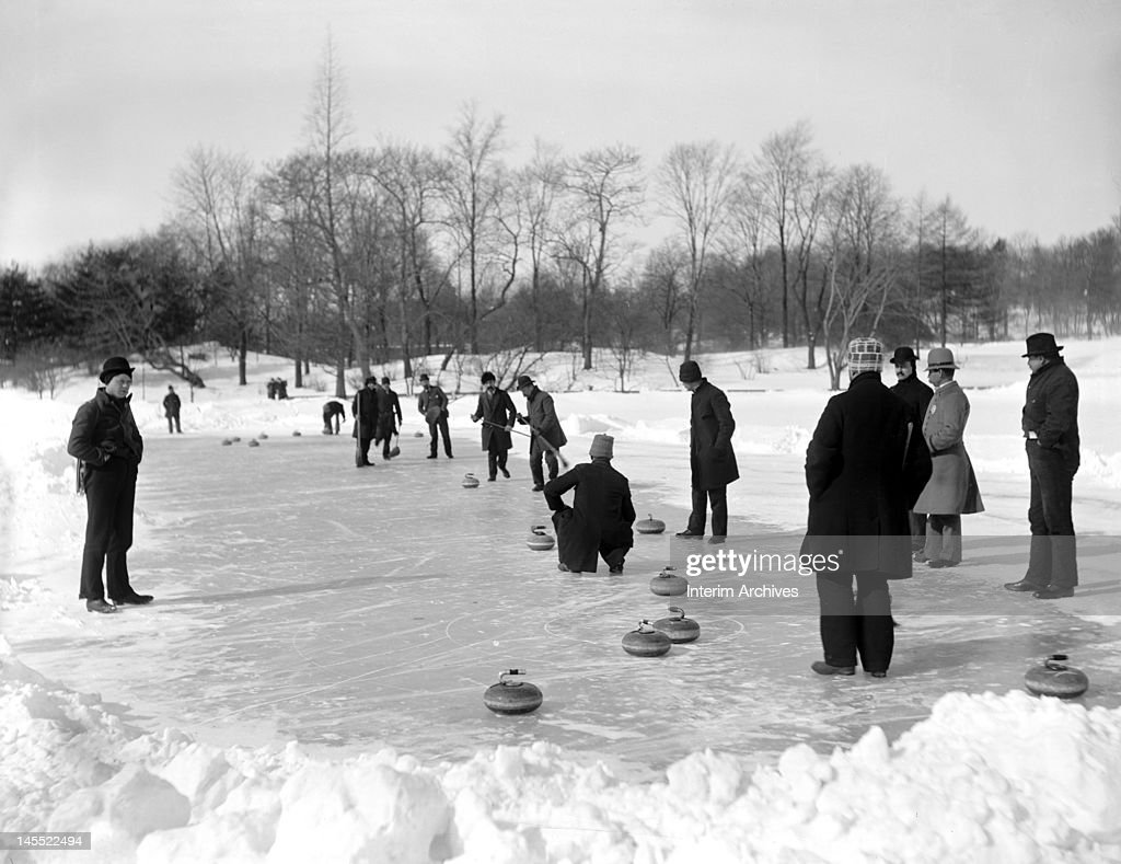 A group of men gather on a frozen pond to enjoy the sport of curling, in Central Park, New York, early twentieth century.