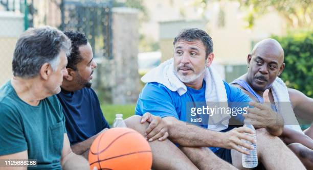 group of men hanging out on basketball court, talking - only men stock pictures, royalty-free photos & images
