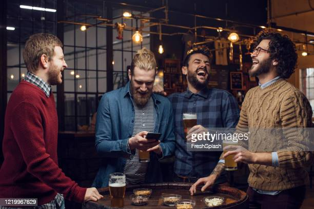 group of men having a laugh at the pub while drinking beer and watching a football game on the mobile phone - small group of people stock pictures, royalty-free photos & images