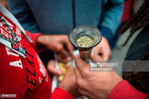 A group of men hold a bottleneck pipe filled with marijuana as a crowd of about two thousand people gather to march through the city centre to call...