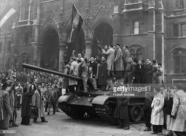 Group of men hold a flag on top of a tank in front of the Parliament building during the Hungarian Revolt, Budapest, Hungary.