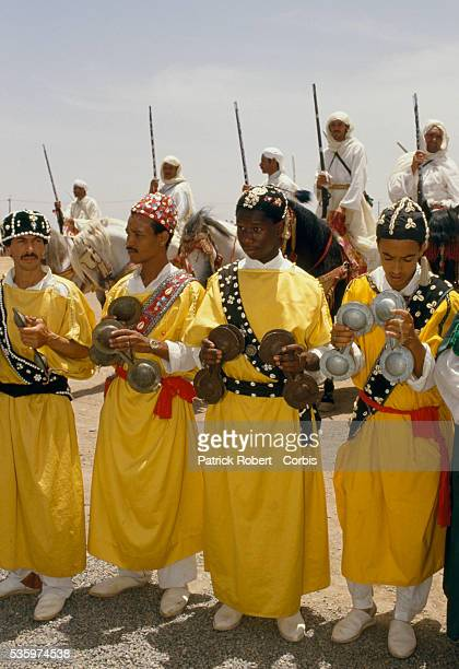 Group of men hold metal instruments at a celebration for the wedding of Princess Lalla Asmaa, daughter of Hassan II, King of Morocco.
