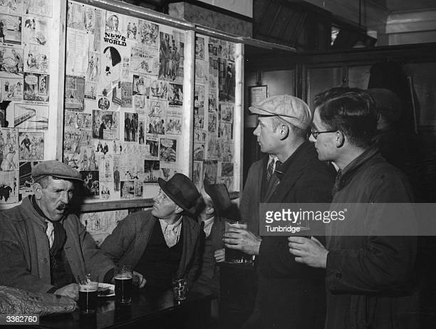 A group of men in a pub look over a selection of wartime cartoons on display in the pub lounge