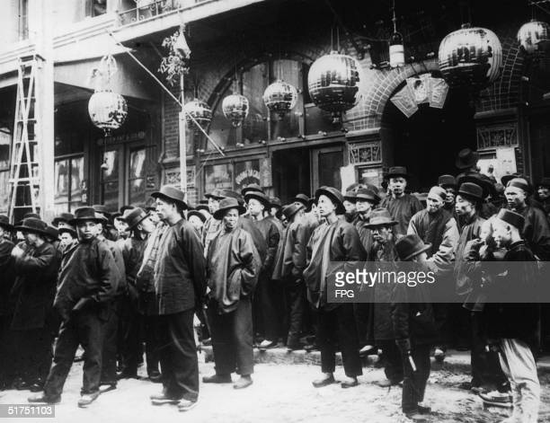 A group of men in Asian jackets and shoes wear hats and stand on the sidewalk and in the street below paper lanterns outside the Yuen Fat Co premises...