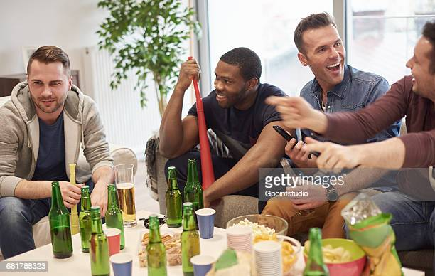 Group of men in lounge sitting around table with beer bottles and snacks talking, smiling
