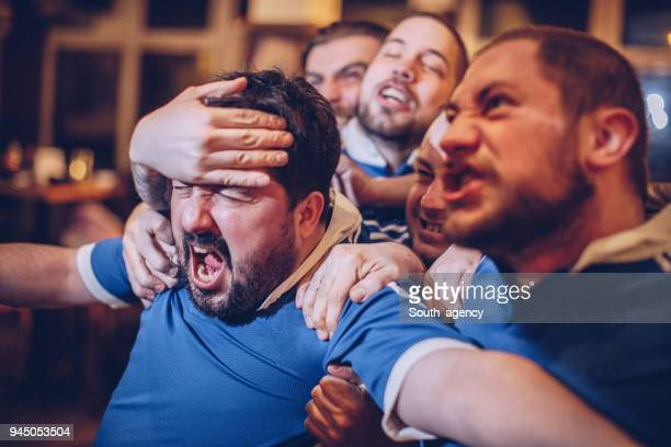 group of men in sports pub - american football sport stock pictures, royalty-free photos & images