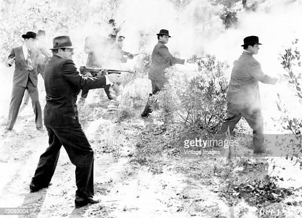 A group of men in suits and hats are obscured by the smoke from the guns including Thompson submachine guns shotguns and revolvers that they are...