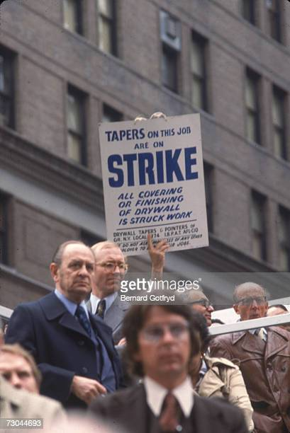 A group of men in suits and overcoats probably union officials stand in solidarity as a man from the Drywall Tapers and Pointers of Greater New York...