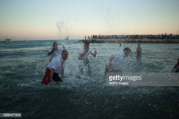 A group of men in traditional costumes are seen playing with the water on the beach after the procession of the Virgen del Carmen brotherhood Every...