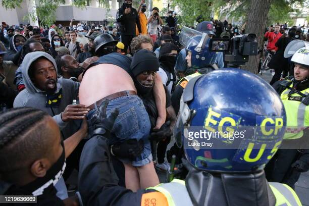 A group of men including Patrick Hutchinson help an injured man away after he was allegedly attacked by some of the crowd of protesters as police try...