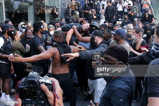 A group of men including Patrick Hutchinson help an injured man away after he was allegedly attacked by some of the crowd of protesters on the...