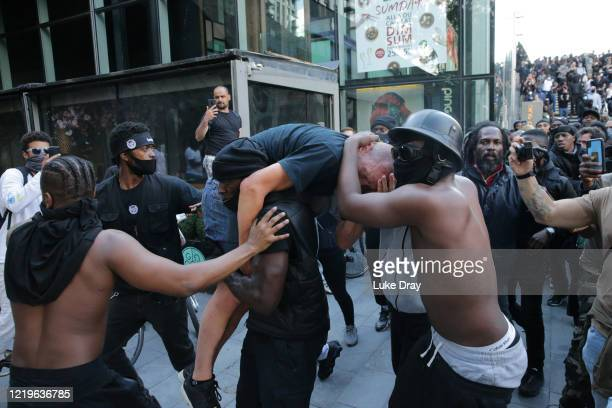 Group of men including Patrick Hutchinson help an injured man away after he was allegedly attacked by some of the crowd of protesters on the...