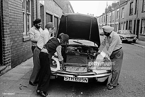 A group of men inspect a car engine in Leeds 1983