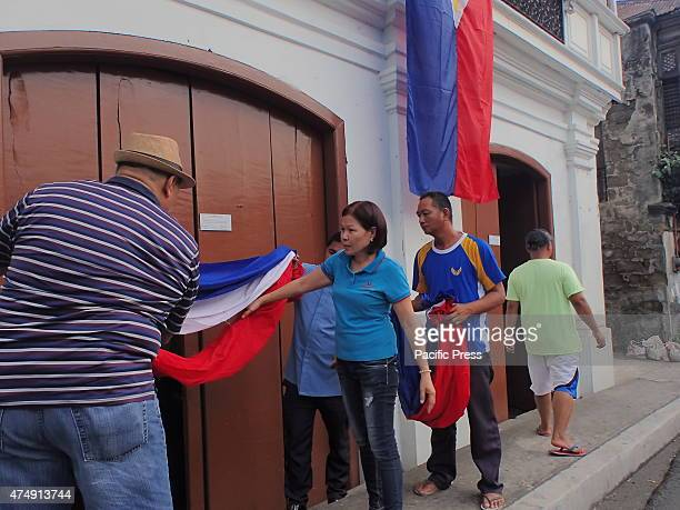 Group of men installing flags on the ancestral houses in Taal Batangas in time of National Flag Day which is celebrated around the Philippines every...