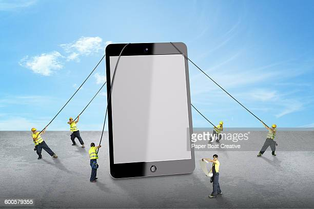 group of men lifting a giant tablet device