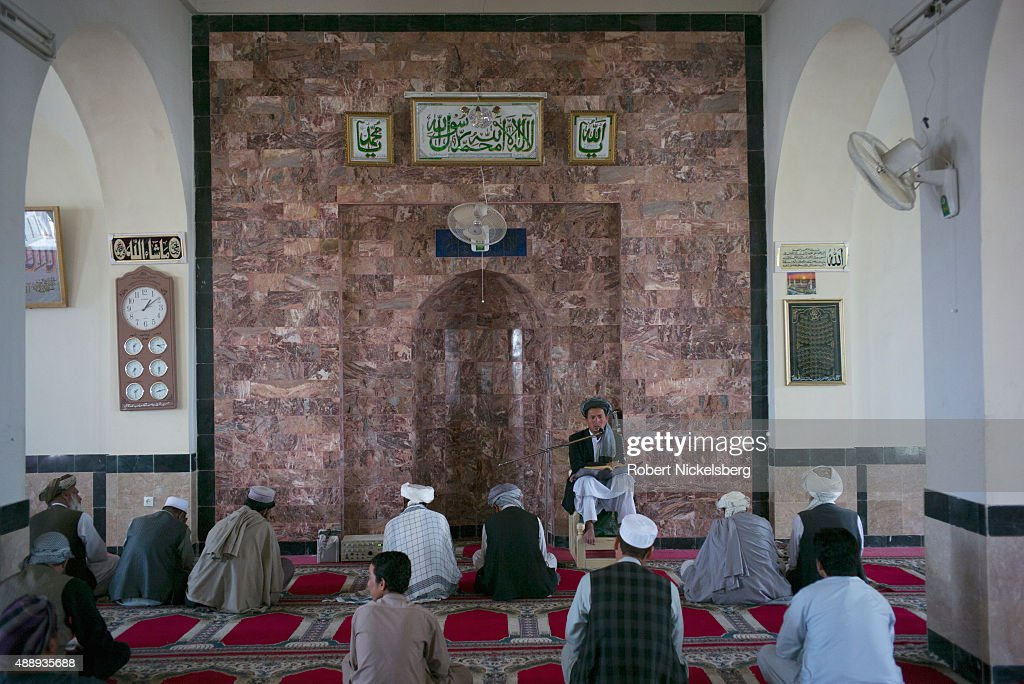 A group of men listen to a mullah offer a sermon at the Shah Agha shrine September 4, 2015 during the traditional Friday prayer service in Kabul, Afghanistan.