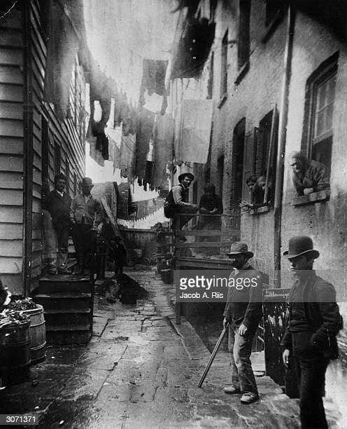 A group of men loitering in an alley known as 'Bandits' Roost' situated off Mulberry Street in New York City