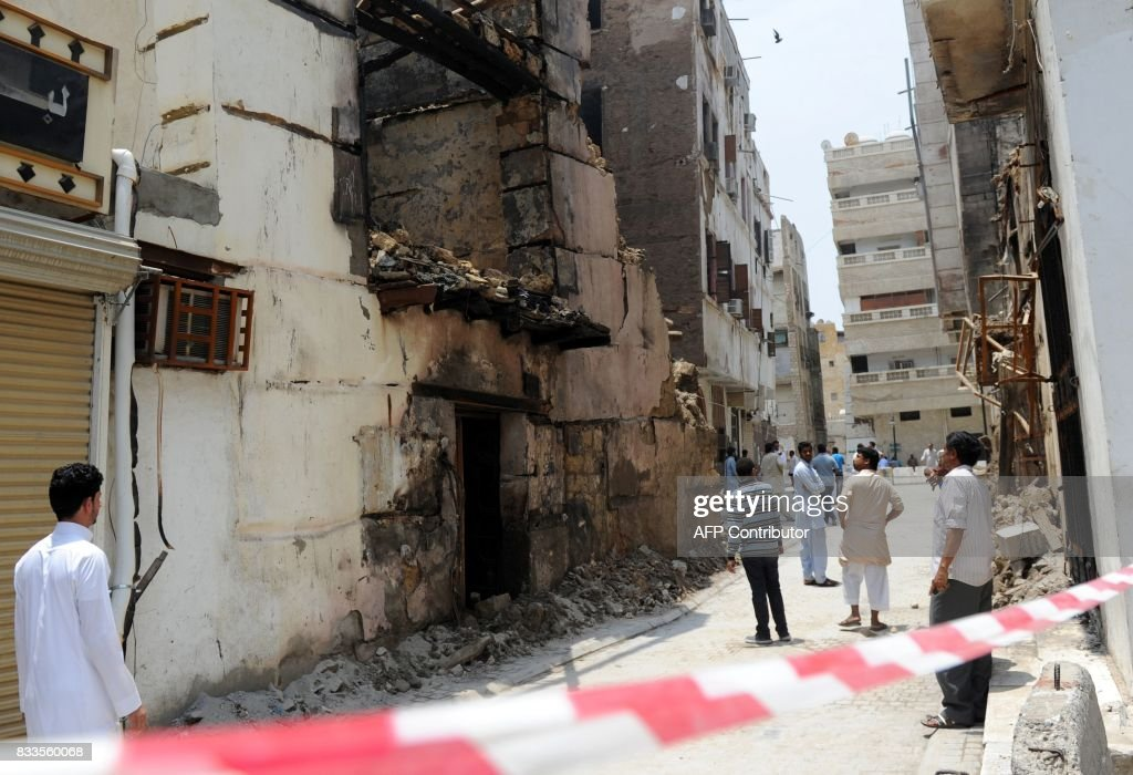 A group of men look at a destroyed building in the traditional section of the Saudi Red Sea port city of Jeddah on August 17, 2017, following a blaze the previous day which damaged three buildings in the UNESCO world heritage site. Saudi civil defence said 60 people had evacuated their homes when the fire broke late on August 16 in al-Balad, a historic district in the city which dates back to the 8th century. / AFP PHOTO / Amer HILABI