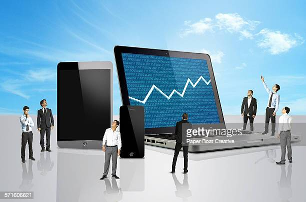 Group of men looking at a laptop with stocks mark