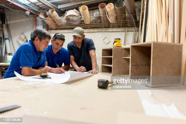 group of men making furniture together at the carpentry - hispanolistic stock photos and pictures