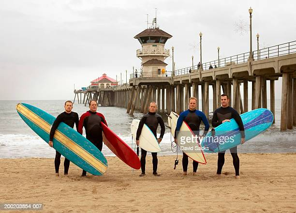 Group of men on beach with surfboards, portrait