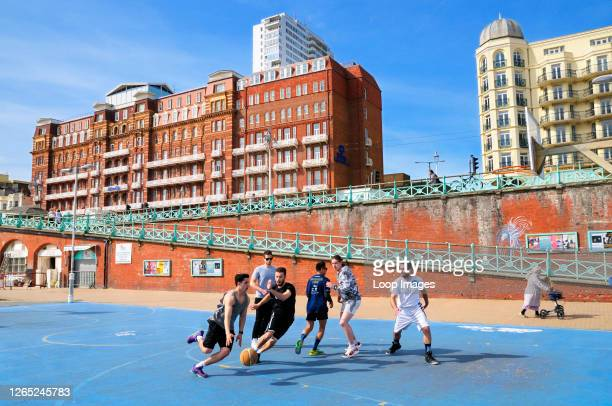 A group of men playing basketball on Brighton seafront