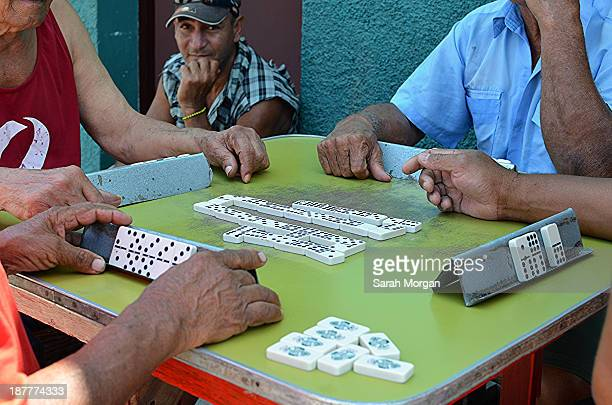 Group of men playing dominoes in the street in Cardenas, Matanzas, Cuba. Despite the social, political and economic change happening in Cuba many...