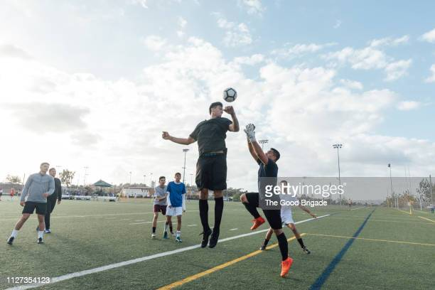 group of men playing pick up soccer game - match sportivo foto e immagini stock