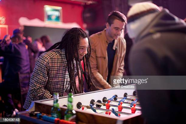 group of men playing table football in bar - club football stockfoto's en -beelden