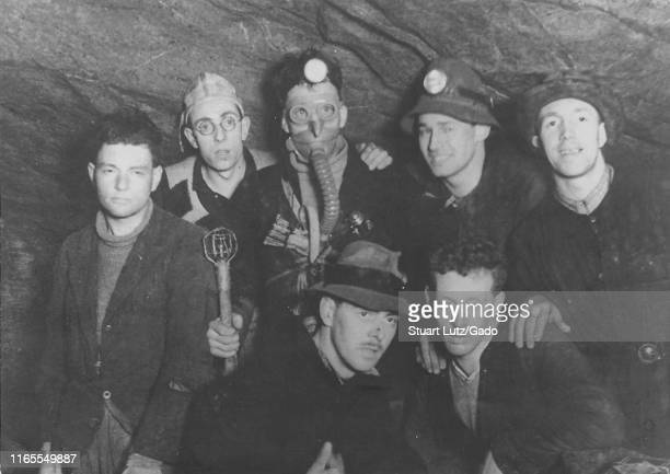 A group of men pose underground in a cave some wearing respirators miner's lamps and other gear during a Northern Cavern and Fell Club rock climbing...
