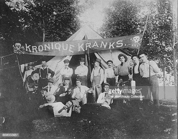 A group of men pose with an assortment of banjos guitars fishing rods rifle and axes in front of a Civil Warera wedgeshaped tent and a banner reading...