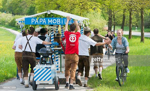 A group of men pull their 'Papamobil II' equipped with a beer barrel and a barbecue over a cycle track near Wessling southern Germany on father's day...