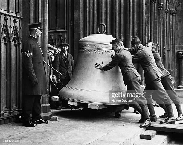 Group of men push a bell into York Minster ready for re-hanging.
