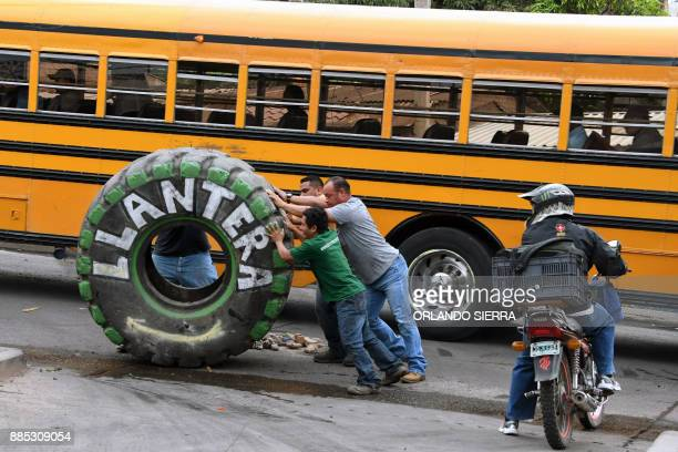 A group of men push a tractor wheel to clear a road where supporters of the presidential candidate for Honduras' Opposition Alliance against the...