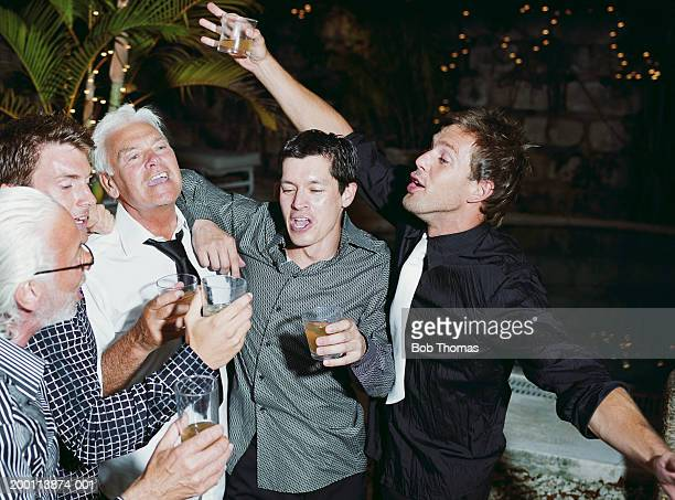 Group of men raising toast outdoors, night